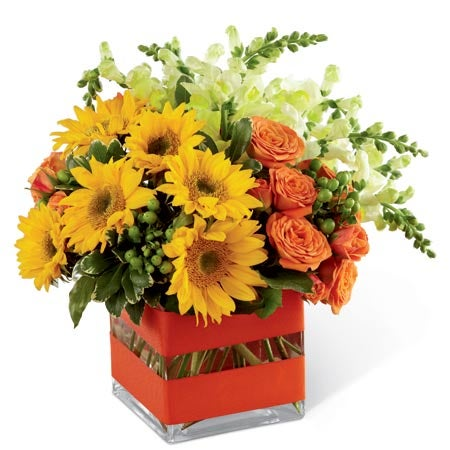A floral combination of mini sunflowers, orange spray roses, yellow snapdragons, and green hypericum berries