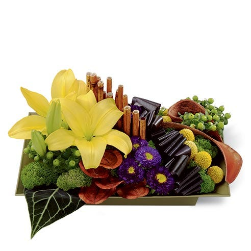 Floral arrangement of yellow asiatic lilies, purple matsumoto asters, green hypericum berries, yellow craspedia, red ti leaves, anthurium leaves, dyed river cane stems, land lotus petals, and elephant ear pods