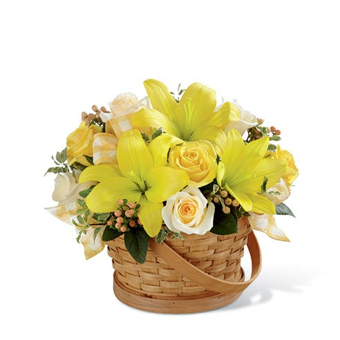Yellow roses, cream roses, yellow LA hybrid lilies, peach hypericum berries and greens in a woven woodchip handled basket
