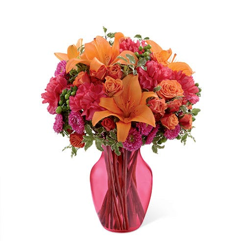 Floral arrangement of orange spray roses, orange Asiatic lilies, hot pink matsumoto asters, fuchsia carnations, and green hypericum berries