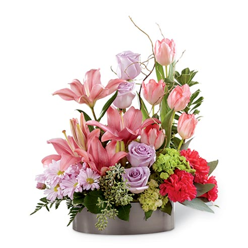 Lavender roses, pink tulips, fuchsia carnations, pink Asiatic lilies, lavender daisies, green mini hydrangea and an assortment of greens with curly willow tips in a metal oval container