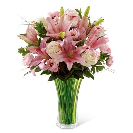 Bi-colored pink and white roses, pink ranunculus, pink Asiatic lilies, bear grass & lush greens arranged in a green flared glass vase