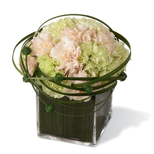 Peach carnations, light green carnations, and lily grass in a clear glass cubed vase