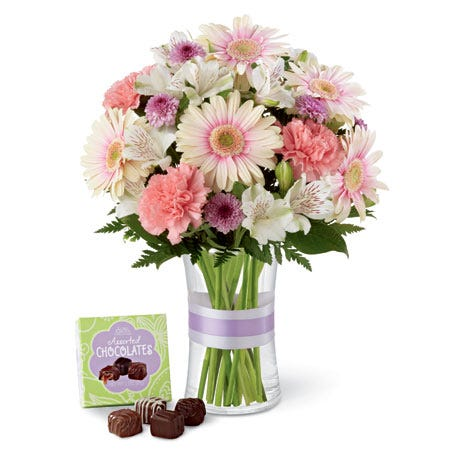 White pink gerbera daisy bouquet with a small box of chocolates