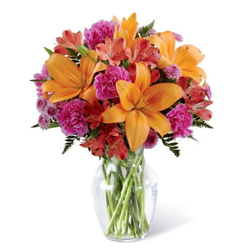 Orange lilies and pink carnations flower bouquet arrangement in a glass vase