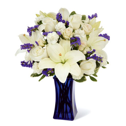 A white and blue flower bouquet with blue statice, white lilies and white roses