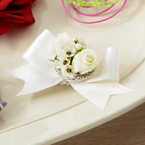 Wristlet with white spray roses and white waxflower brought together with an ivory satin ribbon