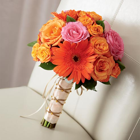 Tied bouquet of orange roses, spray roses, and gerbera daisies arranged with fuchsia roses all tied together at the stems with peach satin ribbon