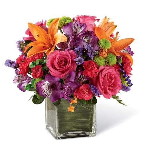 Pink roses, orange lilies, purple peruvian lily and a square glass vase