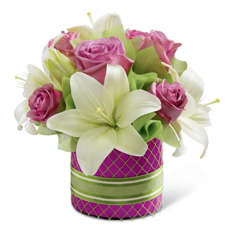 Lavender roses and white Asiatic lilies in a cylinder glass vase