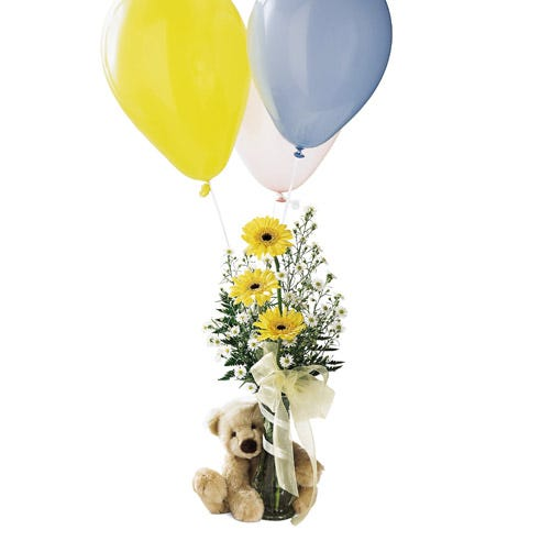 Yellow gerbera daisies are in a vase with a teddy bear and balloon