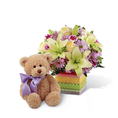 Cream roses, white Asiatic lilies, lavender daisies, lavender mini carnations, bupleurum and greens in a clear glass cubed vase overlaid with a variety of colorful designer ribbons and delivered with a 10 inch seated plush bear