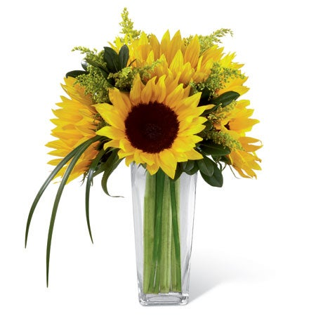 Sunflowers, solidago, and lily grass blades in a clear glass tapered square vase
