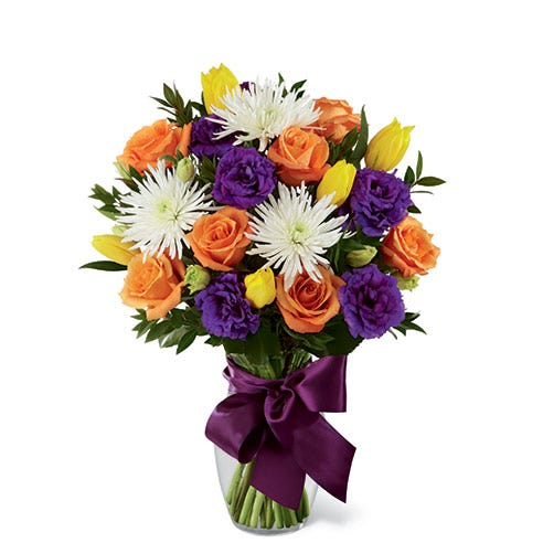 Orange roses, yellow tulips, white spider chrysanthemums, purple double lisianthus and myrtle in a clear glass vase with a mauve satin ribbon