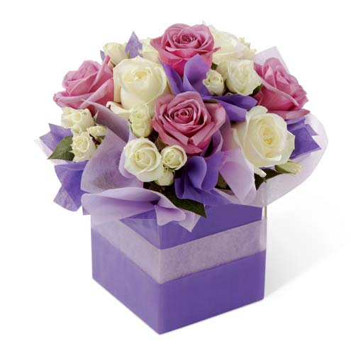 Lavender roses, white roses, and white spray roses in a clear glass cube vase covered in lavender and purple bouquet wrap sheets