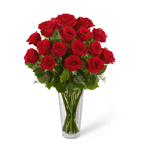 Dozen long stem red roses in classic glass vase with seeded eucalyptus