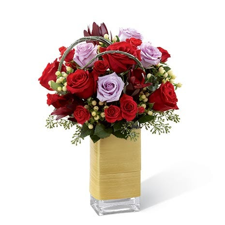 Red roses, lavender roses, red spray roses, white hypericum berries, and lush greens in a clear glass vase