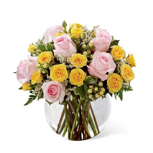 Pink roses, yellow spray roses, white hypericum berries, and white limonium in a clear glass bubble bowl vase