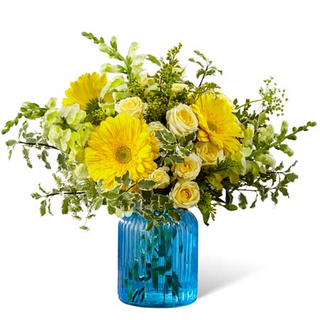 Yellow gerbera daisies paired with yellow spray roses in a blue vase