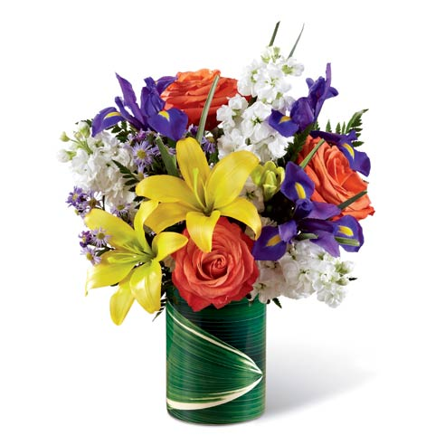 Yellow lily orange rose and white stock flowers bouquet in a leaf wrapped vase