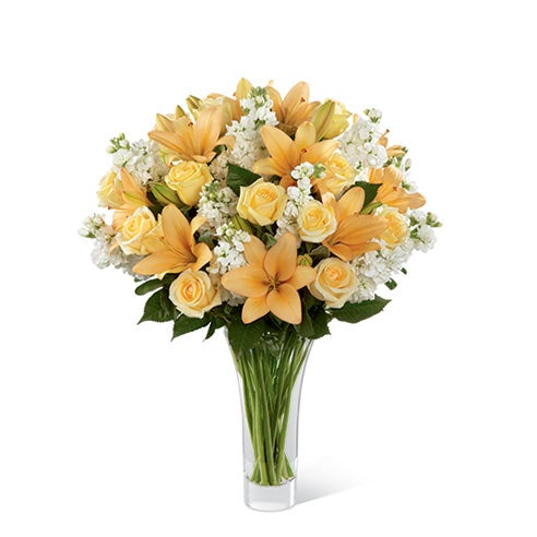 Cream roses, peaceh Asiatic lilies, and white stock in a superior flared clear glass vase