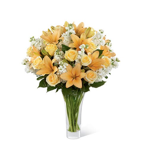 Cream roses, peach lilies, and white stock in a premium flower bouquet