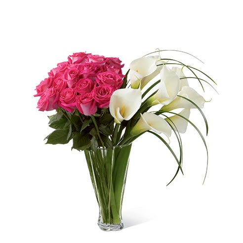 Fuchsia roses, open-cut calla lilies, and lily grass blades in a superior clear glass twist vase