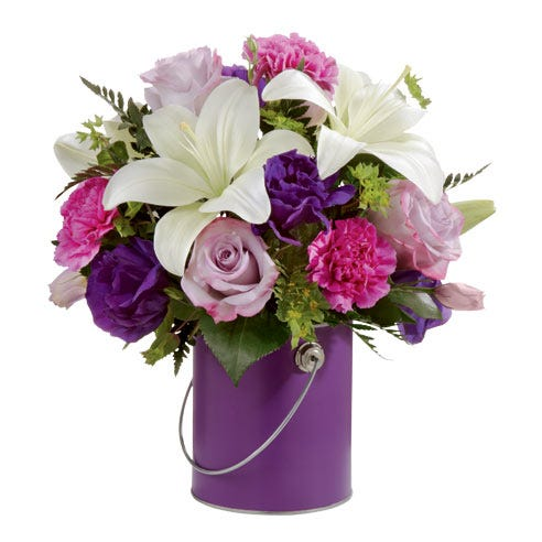 White lilies and lavender roses with pink carnations in a purple paint can vase