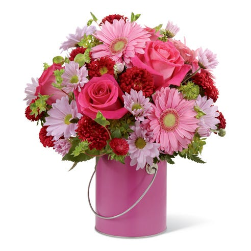 Pink Gerber daisies, pink roses, purple daisies all in a pink paint vase