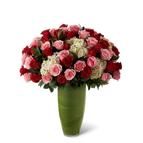 Premium long-stemmed red roses, premium long-stemmed pink roses, pink hydrangea, lush greens, and exotic foliage in a superior 14-inch clear glass bullet vase