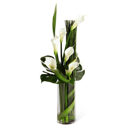 White calla lilies in cylinder vase with greens