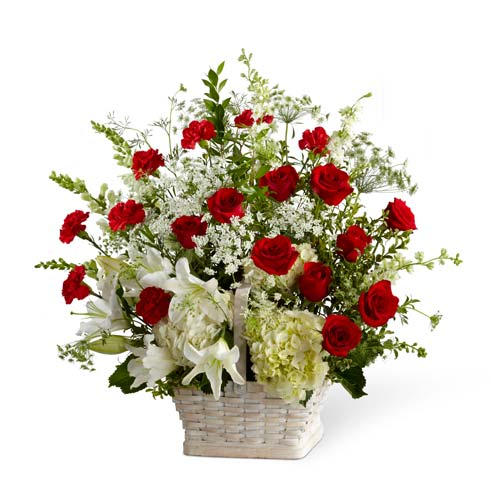 Basket sympathy arrangement with red roses, carnations and white hydrangea