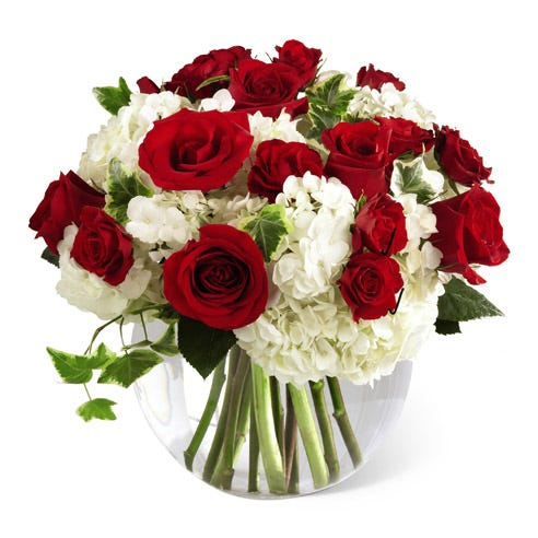 Red roses, white hydrangea and red spray roses in circular glass vase