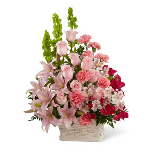 Pink roses, pink lilies and fuchsia carnations in woven basket for delivery