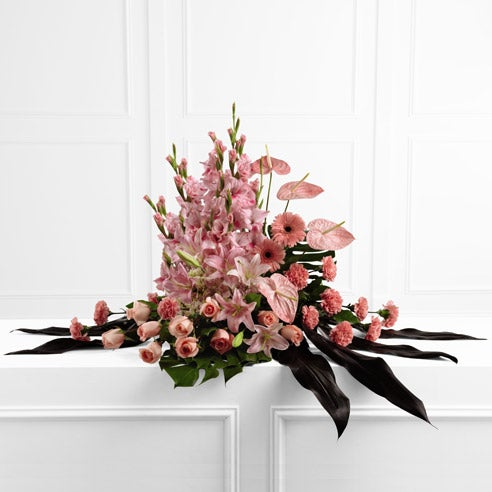 Sympathy arrangement for delivery with pink roses, carnations and oriental lilies