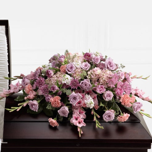 Purple and pink flowers delivered in a casket spray