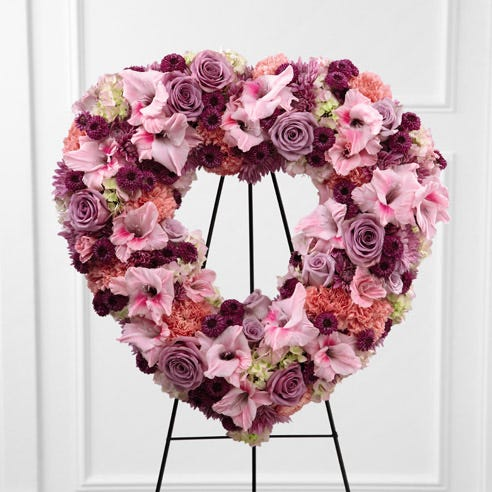 Funeral standing spray with purple roses, pink carnations and gladiolus in heart shape