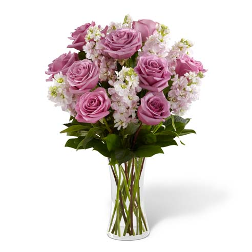Purple roses, pink flowers and greens in clear vase