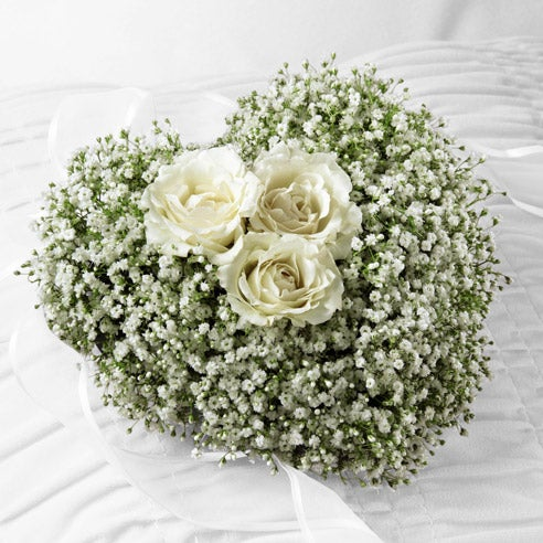 Baby's breath and white spray roses in a heart-shaped arrangement