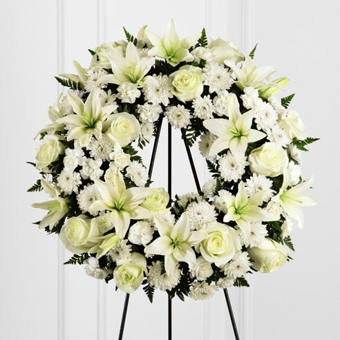 White roses, white lilies and carnations in a sympathy standing wreath