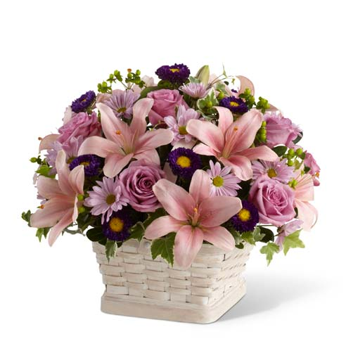 Purple roses, pink lilies and purple daisies in woven basket for a sympathy flowers