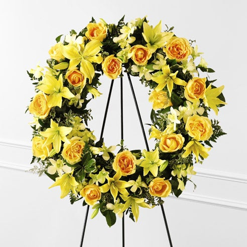 Yellow roses and yellow lilies in a sympathy wreath