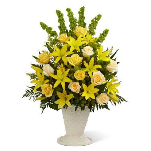Yellow lilies and cream roses in container for sympathy gift