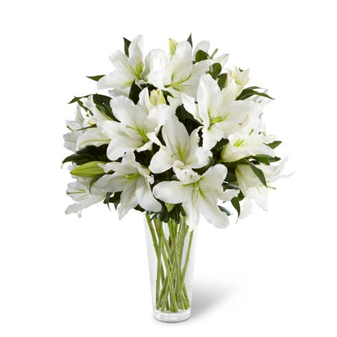 White oriental lilies and greens arranged in glass vase