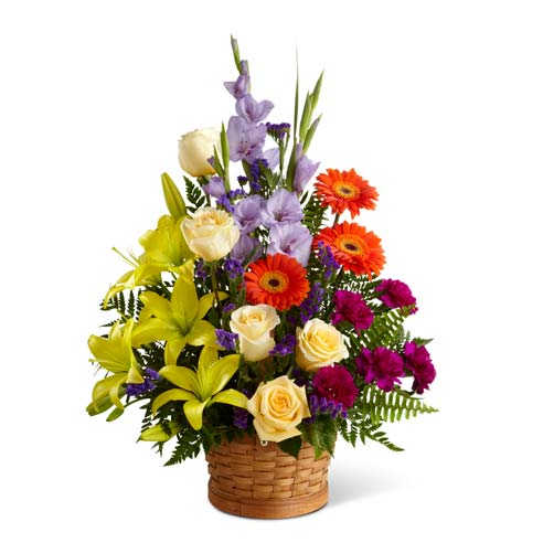 Yellow roses, yellow asiaitic lilies and purple flowers in a funeral floral basket