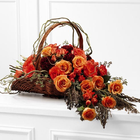 Orange roses in an orange flower centerpiece in whicker basket with cheap flowers
