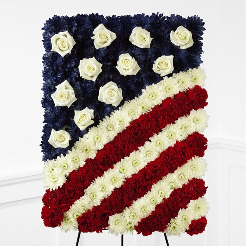 Red carnations, white chrysanthemums and blue dyed white chrysanthemums to look like an American flag w/ white roses as the stars