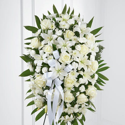 Sympathy spray for delivery with white roses, lilies and carnations