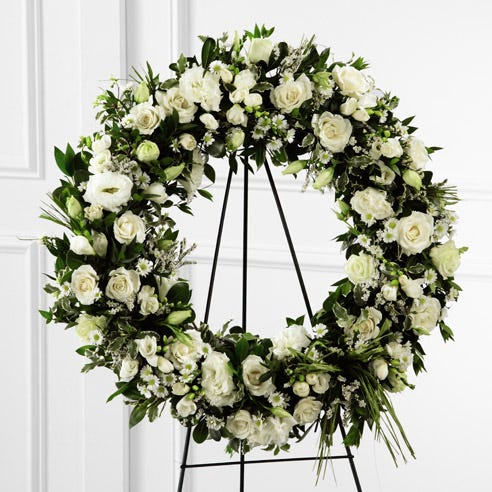Sympathy white flower wreath standing spray with roses, lisianthus, and freesia