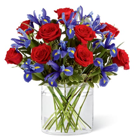 Red roses with purple irises in unique glass vase for cheap flower delivery